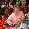 Cari Clement teaches machine knitting to refugee women in Rwanda.